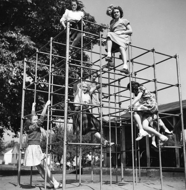 Female students sitting and playing on a playground structure.